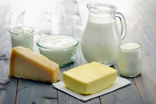 Jug of milk with pat of butter yoghurt and cheese