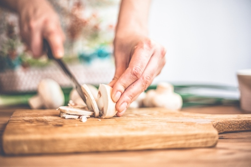 Woman chopping mushrooms with knife on cutting board.