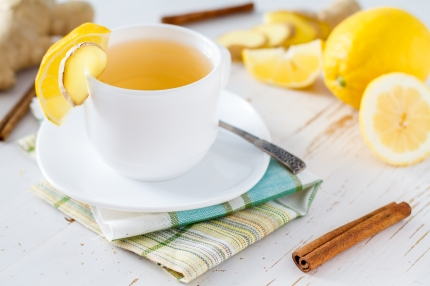 Tea in white cup with ginger, lemon, cinnamon and honey