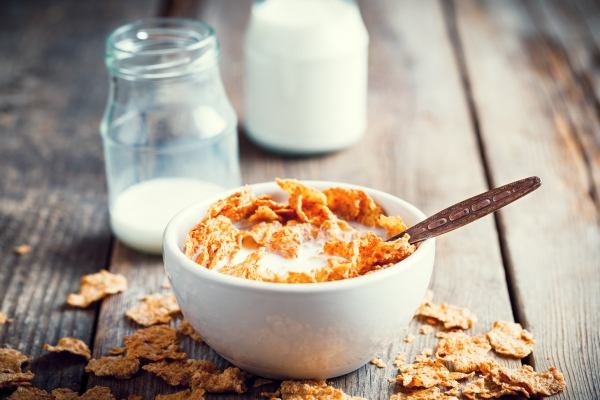 Breakfast cereal wheat flakes in bowl and milk bottles